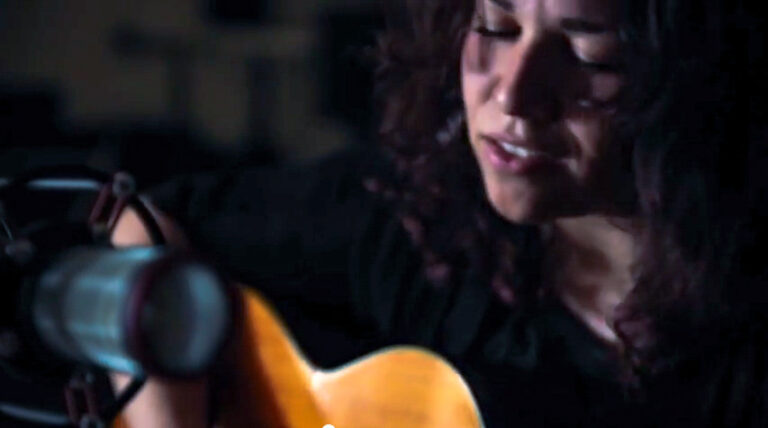 consultant Sonia Montez with guitar in front of microphone